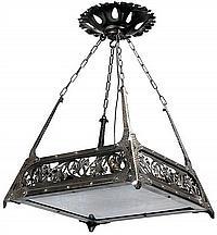 Louis MAJORELLE (1859-1926) Petit lustre en métal, patine noire, présentant une structure tronconique martelée formant crosses et dé...