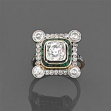 Bague diamant coussin vers 1910 Elle est ornée d'un diamant coussin (TA) en serti clos dans un double entourage d'émeraudes calibrée...