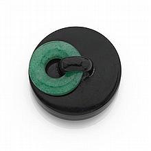 CARTIER époque art déco Boîte à pilules de forme ronde en argent laqué noir. La prise mobile en jade jadéite vert. Travail français,...