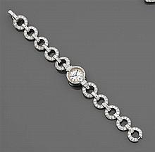 CARTIER années 1935 Montre-bracelet de dame à boîtier rond retenu par des maillons ronds. L'ensemble est rehaussé de diamants taille...