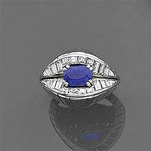 Années 1950 Bague chevalière saphir Elle est ornée d'un saphir ovale en chaton à griffes sur deux lignes de diamants baguette dispos...