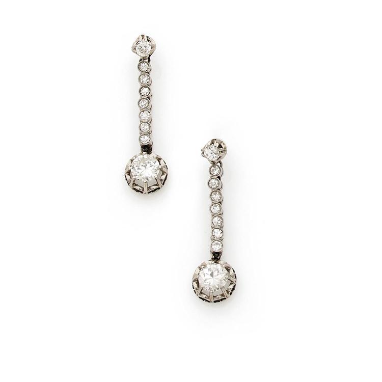 A diamond and platinum pair of ear pendants, circa 1920.