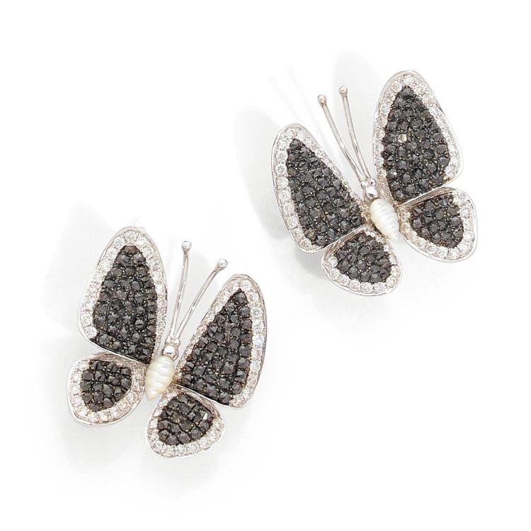 A mother of pearl, black diamond, diamond and gold ear clips.