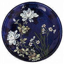 Edmond LACHENAL (1855-1948) Plat circulaire en faïence sur talon à décor émaillé polychrome d'une composition florale sur fond bleu nui