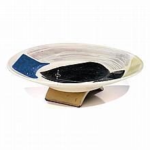 MADO JOLAIN (NÉE EN 1921) Grand plat circulaire creux en faïence sur talon formant arcature, décor d''un poisson émaillé noir et de...