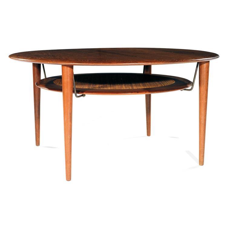 PETER HVIDT (1916-1989) Table basse circulaire, structure en teck, plateau à ceinture profilée, piétement fuselé, chapiteaux circu...