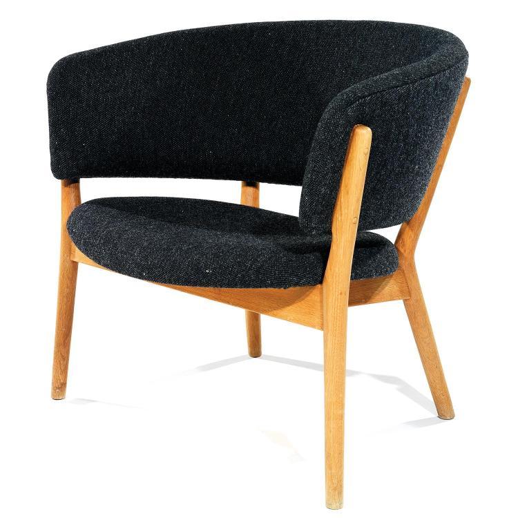 NANNA DITZEL (1923-2005)Grand fauteuil bas à structure en chêne clair, piétement quadripode fuselé profilé en V maintenant la traver...