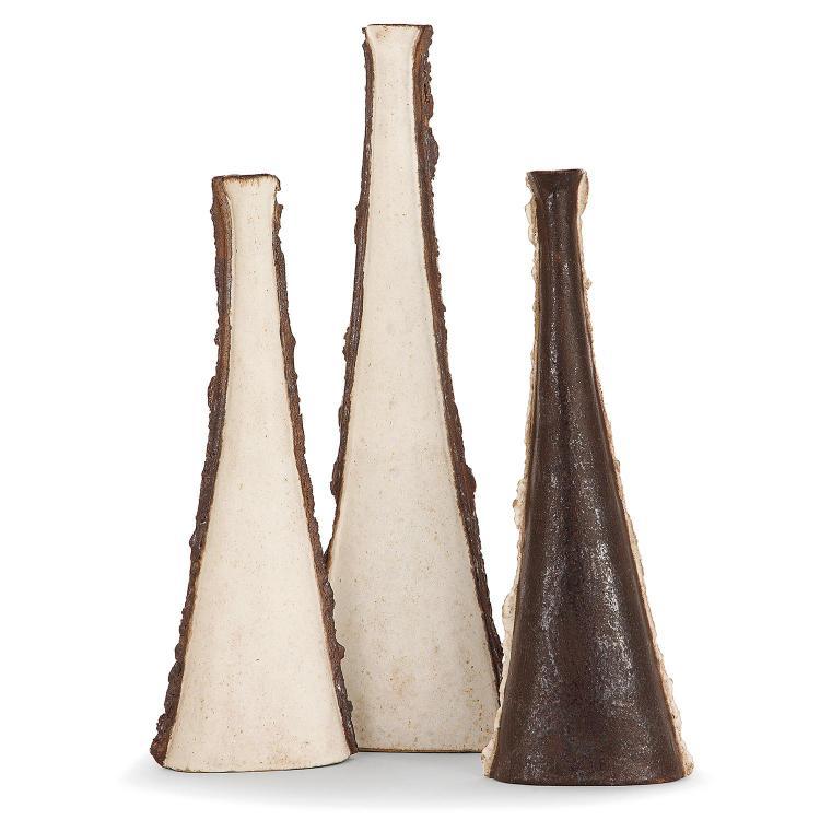 BRUNO GAMBONE (NÉ EN 1936) Suite de trois bouteilles en grès à corps triangulé méplat bordé de ressauts verticaux festonnés émaill...