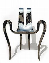 GUILLAUME PIÉCHAUD (NÉ EN 1968). A partly hammered mirror-polished stainless steel armchair, 2012, from an edition of 8. Stamped with t