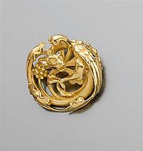 WIESE années 1860 Broche chimère de forme ronde en or jaune ciselé. Elle représente une chimère ailée en ronde-bosse dans un entoura...