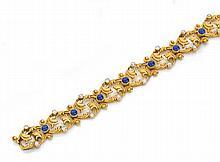 Années 1900 Bracelet saphirs Il est composé de maillons à décor de feuillages en or jaune 18K rehaussés d'un cabochon de saphir et d...