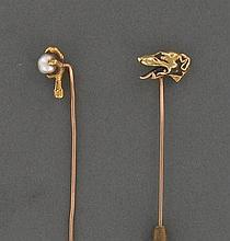 LOT DE 2 EPINGLES DE CRAVATE  en or jaune, l'une représentant une serre d'aigle retenant une perle fine baroque (non testée), l'autre une tête de chien de profil.