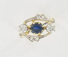 BAGUE CROISEE  en or jaune et or gris 18K, ornée d'un saphir ovale serti en chaton à griffes et épaulé de deux petits diamants.