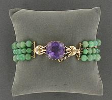 BRACELET  composé de 3 rangs de boules de jade, le fermoir en or jaune orné d'une améthyste taille coussin facetté.