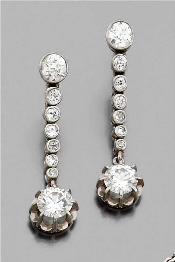 Paire de pendants d'oreilles en or gris, composés d'une ligne de petits diamants en serti clos retenant un diamant taille brillant (...