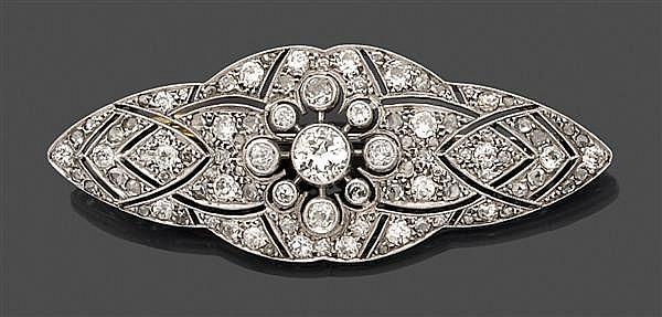 Broche en platine ajouré, de forme oblongue, ornée au centre d'un diamant taille brillant (TA) en serti clos entouré de motifs géomé...