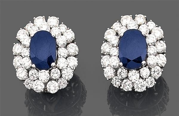 Paire de clips d'oreilles en platine et or gris, ornés au centre d'un saphir ovale dans un double entourage de diamants ronds sertis...