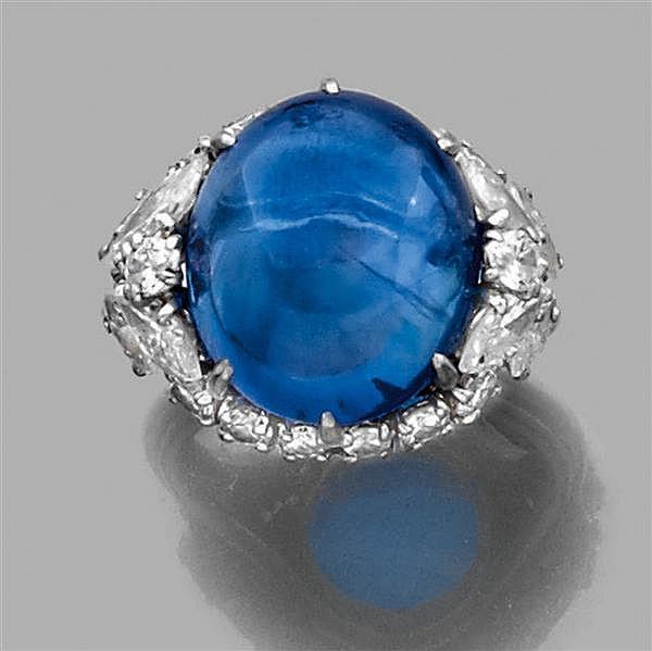 CARTIER Années 1970 Bague en platine, ornée d'un cabochon de saphir dans un entourage de diamants taille brillant et deux motifs feu...