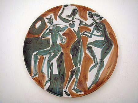Robert PICAULT (1919-2000) Grand plat en faïence sur talon à décor d''un faune jouant de la clarinette et deux femmes nues dansant,...