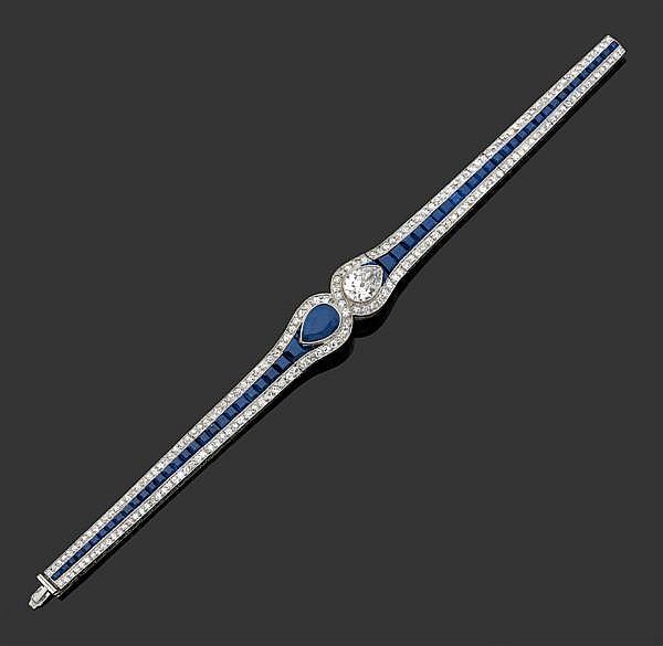 COVEN-LACLOCHE années 1920 Magnifique bracelet souple articulé  en platine, orné au centre d'un diamant poire et d'un saphir poire f...