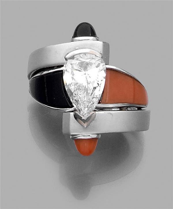 CARTIER Importante Bague asymétrique en or gris satiné et uni, ornée au centre d'un diamant taille poire agrémenté d'onyx et de cora...