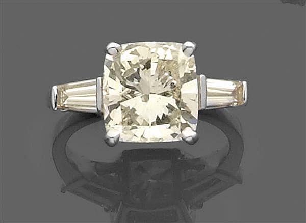 Bague diamant solitaire en or gris, sertie d'un diamant coussin en chaton à griffes encadré par deux diamants trapèze. Travail franç...