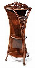 ƒART NOUVEAU Haute sellette d'applique à trois plateaux, en acajou, piétement tripode à décor frontal en découpe de motifs fleuris e...