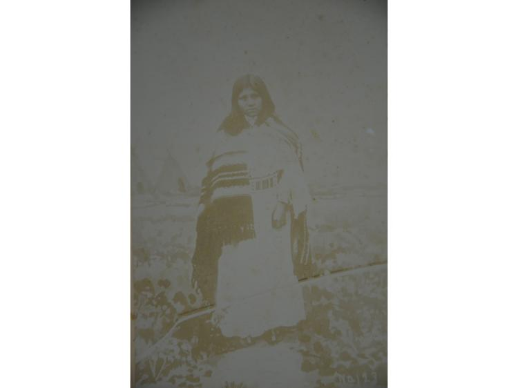 OLD PHOTOGRAPH NATIVE AMERICAN WOMAN WITH TEEPEES IN BACKGROUND.