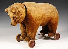 RIDING TOY - Schuco Yes/No Bear on wheels, circa 1930, in caramel mohair with glass eyes, wooden wheels stamped 'Schuco Patent', 24