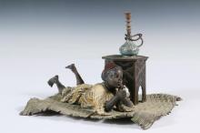 COLD PAINTED AUSTRIAN BRONZE - Bergmann Arab Boy Laying on Wattled Carpet, Smoking a Cigar, alongside a Persian table with hookah, top of which hinges back to reveal an inkwell receiver, (missing bottle), marks on und...