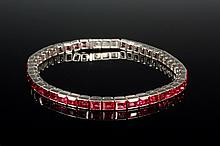BRACELET - Platinum and Ruby Line Bracelet, set with forty-eight well matched calibre cut rubies set in a straight line platinum mounti