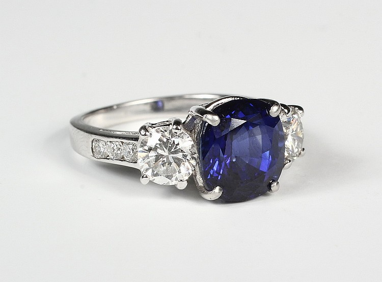 LADY'S RING - Platinum, Diamond and Sapphire Ring, centered with (1) cushion cut blue sapphire flanked on each side by (1) round diamo