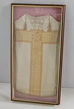 Framed vestment mounted on a pink moire liner