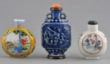 Lot of three Snuff Bottles. China. Two porcelain 19th century bottles. One with a blue glaze and moulded decoration, the other with Famille Rose enamels together with a 20th century Ku Yaeh Hsuan style enameled glass bottle. Largest- 3-3/4