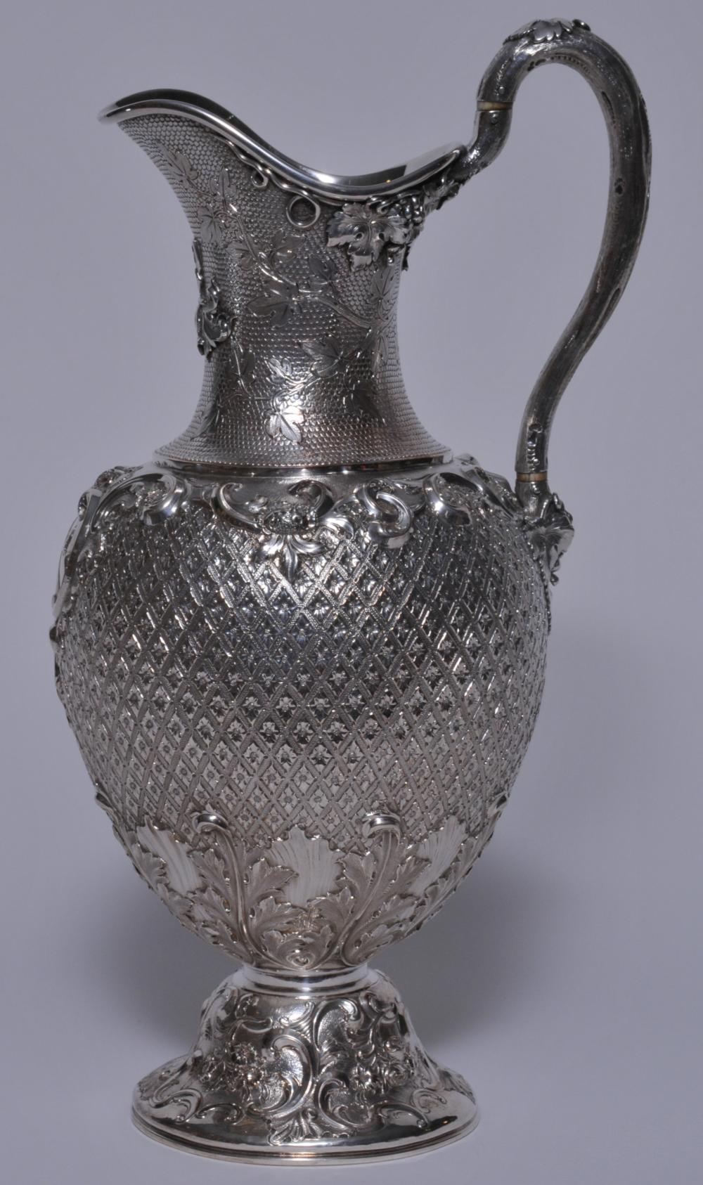 Ornate Scottish Victorian sterling silver ewer. Allover ornate decoration of diamond quilted and stippled ground with relief floral and scroll decoration on body and base. Top with relief grape vine decoration. Large acanthus leaf decoration on lower
