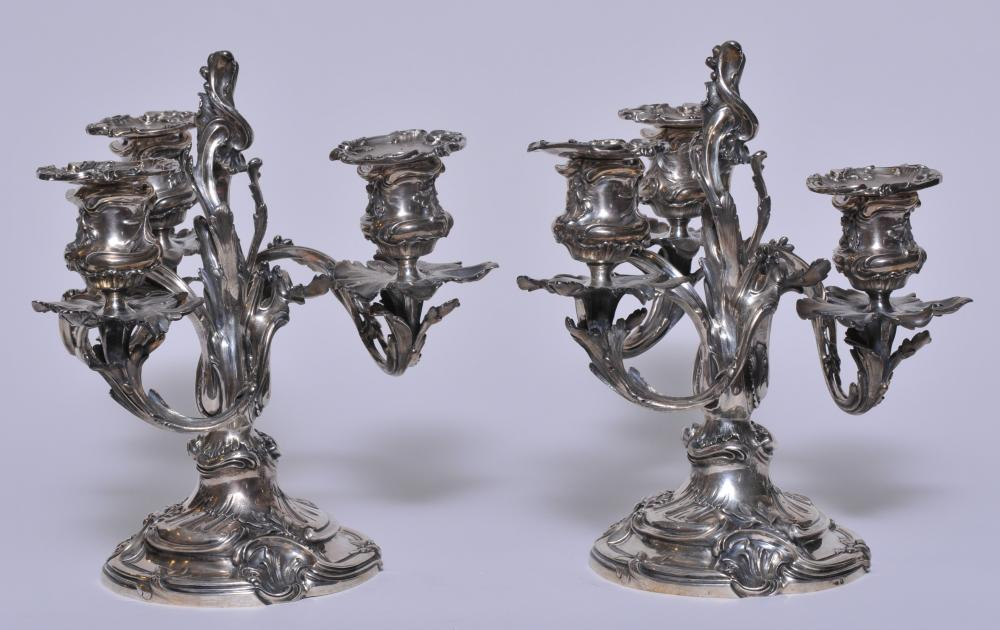 """Lot 2: Pair of """"L. Lapar-Sr De Beguin"""" Paris. French silver three light candelabra. Cast silver Rococco style leaf form branches and decoration. Removable bobeches. Hallmarked on base rims and bobeches. 10-1/2"""" high. A similar pair at Sotheby's, New York. A"""