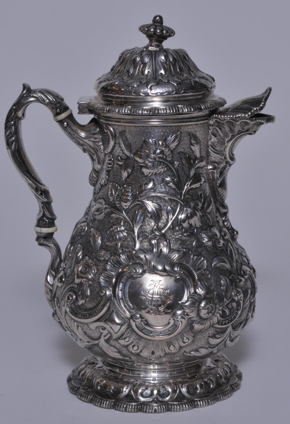 Tiffany & Co. Makers early allover floral repousse decorated covered chocolate pot. Leaf form spout. Lobated base. Cartouche with monogram. Finial pushed down into cover. Handle loose at insulators. Base pushed into body on one side. Early mark. 8-1/
