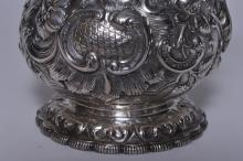 Lot 5: Tiffany & Co. Makers early allover floral repousse decorated covered chocolate pot. Leaf form spout. Lobated base. Cartouche with monogram. Finial pushed down into cover. Handle loose at insulators. Base pushed into body on one side. Early mark. 8-1/
