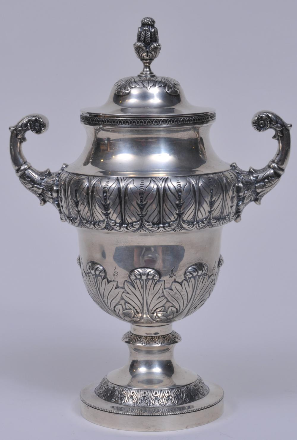"""S. Kirk & Son sterling silver large two handled covered cup. Leaf decorated finial and handles. Leaf repousse decorated beaded and geometric borders. 3/8"""" slight dent on body. Base rim slightly dented. 12"""" high. 1917 inscription on base. 35.5 ozt."""