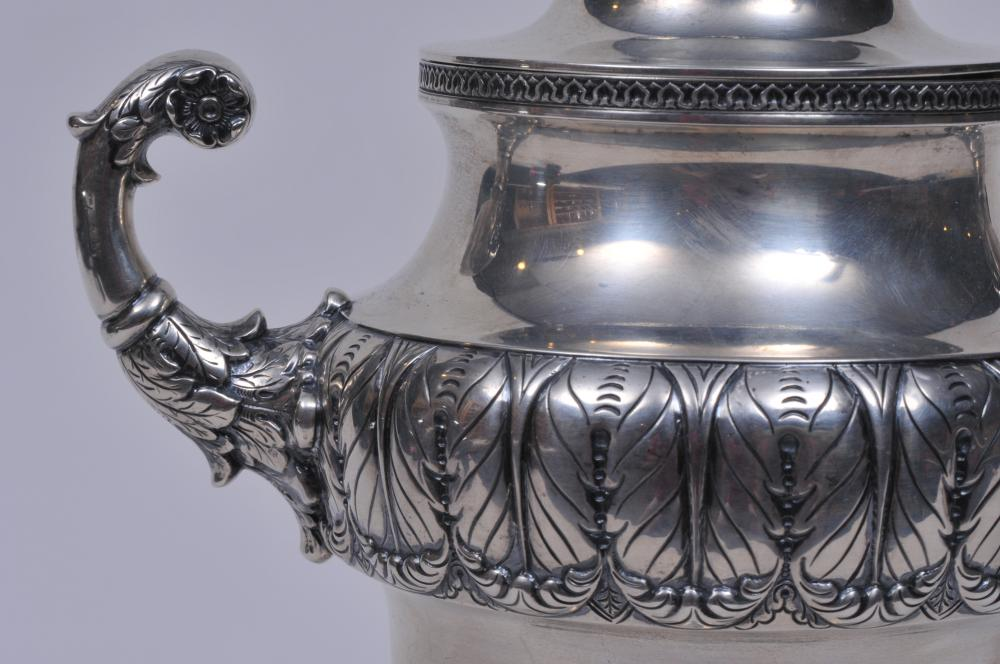 """Lot 10: S. Kirk & Son sterling silver large two handled covered cup. Leaf decorated finial and handles. Leaf repousse decorated beaded and geometric borders. 3/8"""" slight dent on body. Base rim slightly dented. 12"""" high. 1917 inscription on base. 35.5 ozt."""