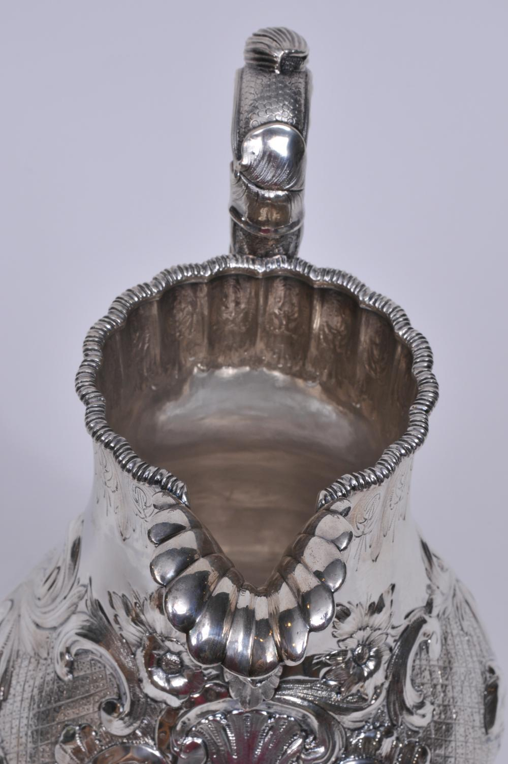 """Lot 12: Early Tiffany & Co. makers. Late """"Tiffany-Young-Ellis"""" large ornate water pitcher. Large acanthus leaf spout. Leaf and vine decorated handle. Leaf-quilted-cartouche decorated body. Monogrammed. Inscription on base rim. 12-1/2"""" high. 37.8 ozt. Good c"""