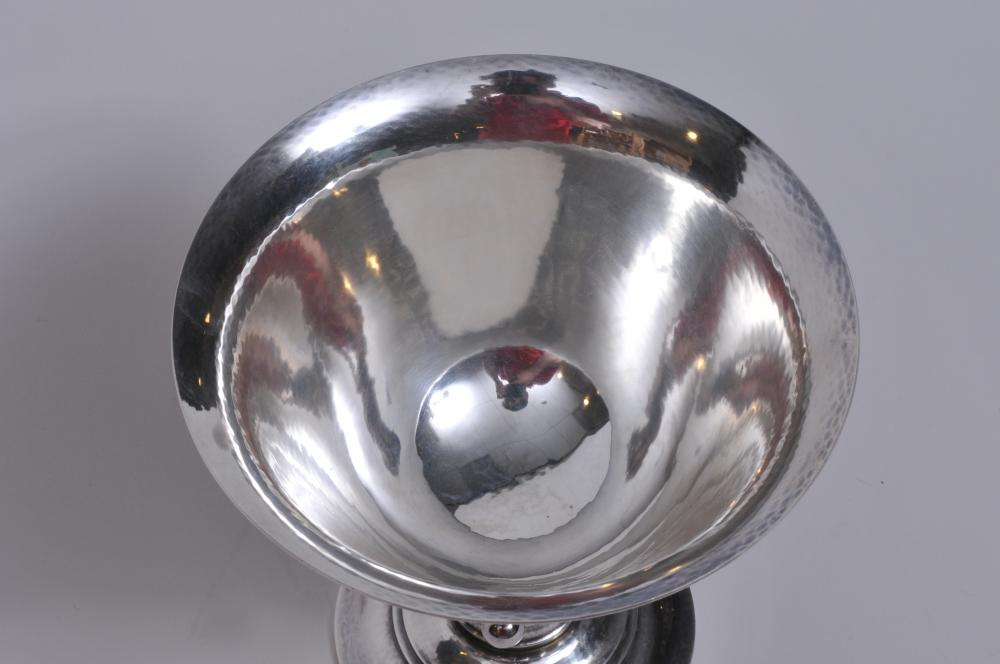 "Lot 14: Georg Jensen. Denmark. Sterling silver footed bowl. Leaf and ball open work decorated stem. Hand hammered surface. Marked on base- ""Dessin"" and with R designer mark. Inscription on 1/8"" base. 5-1/4"" high. 5-5/8"" diameter. 10.1 ozt. Good condition."