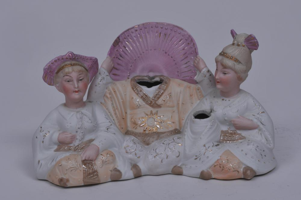 """Lot 18: Early 20th century Continental bisque porcelain Orientalist design nodder group figure. Central Asian figure with nodding head. Asian dressed women on either side. One with nodding fan. Flake chip on pink lustre collar behind central figure. 7-1/2"""""""