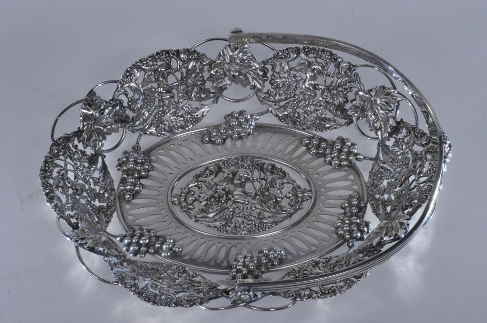 """Large 19th century sterling silver heavy handled basket with pierced figural and grape pattern decoration. Cupid with bow and large relief grapes and leaves. Marked inside handle- Shreve Crump and Low Inc. Sterling. F date mark. 8-3/4"""" w. 7-1/4"""" d."""