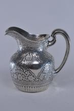"""Lot 25: Gorham sterling silver allover floral and geometric decorated small pitcher. Relief decoration against a stippled ground. Monogrammed. 6-1/4"""" high. 12.2 ozt. Tiny dings on base."""