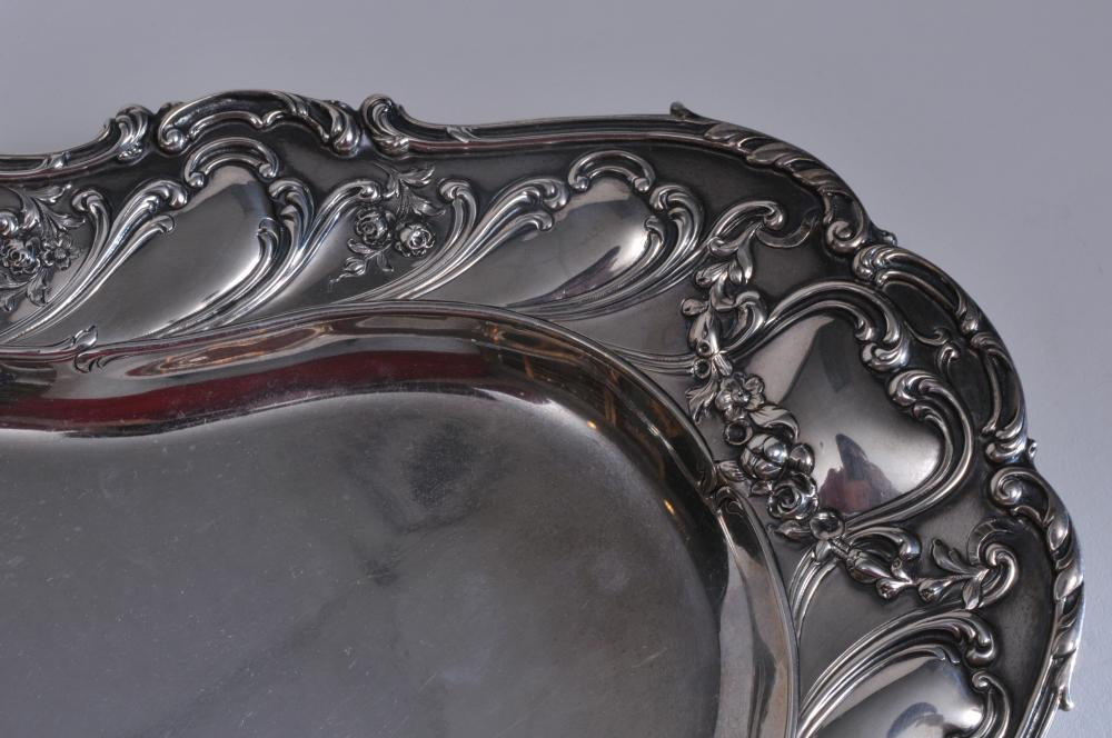 """Lot 30: Large sterling silver oval form tray. Relief floral, leaf and scroll decoration. 18-1/2"""" x 12-3/4"""". Mark worn. Possibly Gorham. 36.9 ozt. Good condition."""