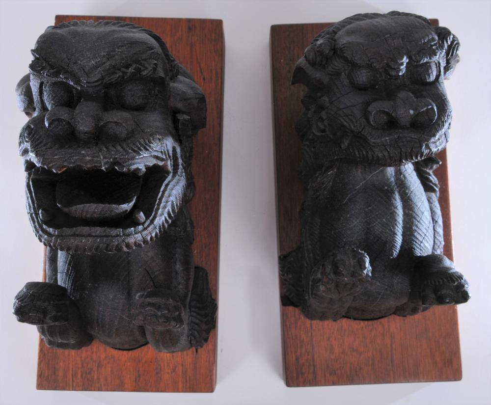 """Pair of antique Asian carved wood Buddhist liion figures mounted to later wood wall mounts. Figures- 10-1/2"""" high. Overall size: 15"""" high. 7"""" wide. There are some architetural elements. Some loss."""
