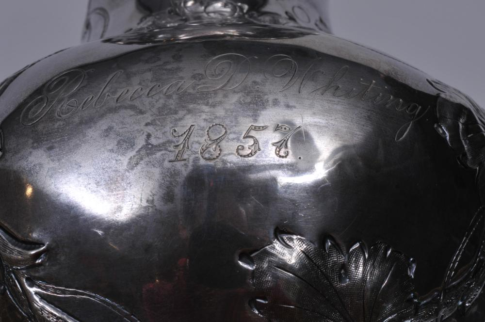 "Lot 44: W.D. Whiting & Co. pure coin silver grape vine repousse decorated ewer. Branch form handle. ""Rebecca Whiting 1857"" inscription. Hallmarked on base. 11-3/4"" high. 21 ozt."