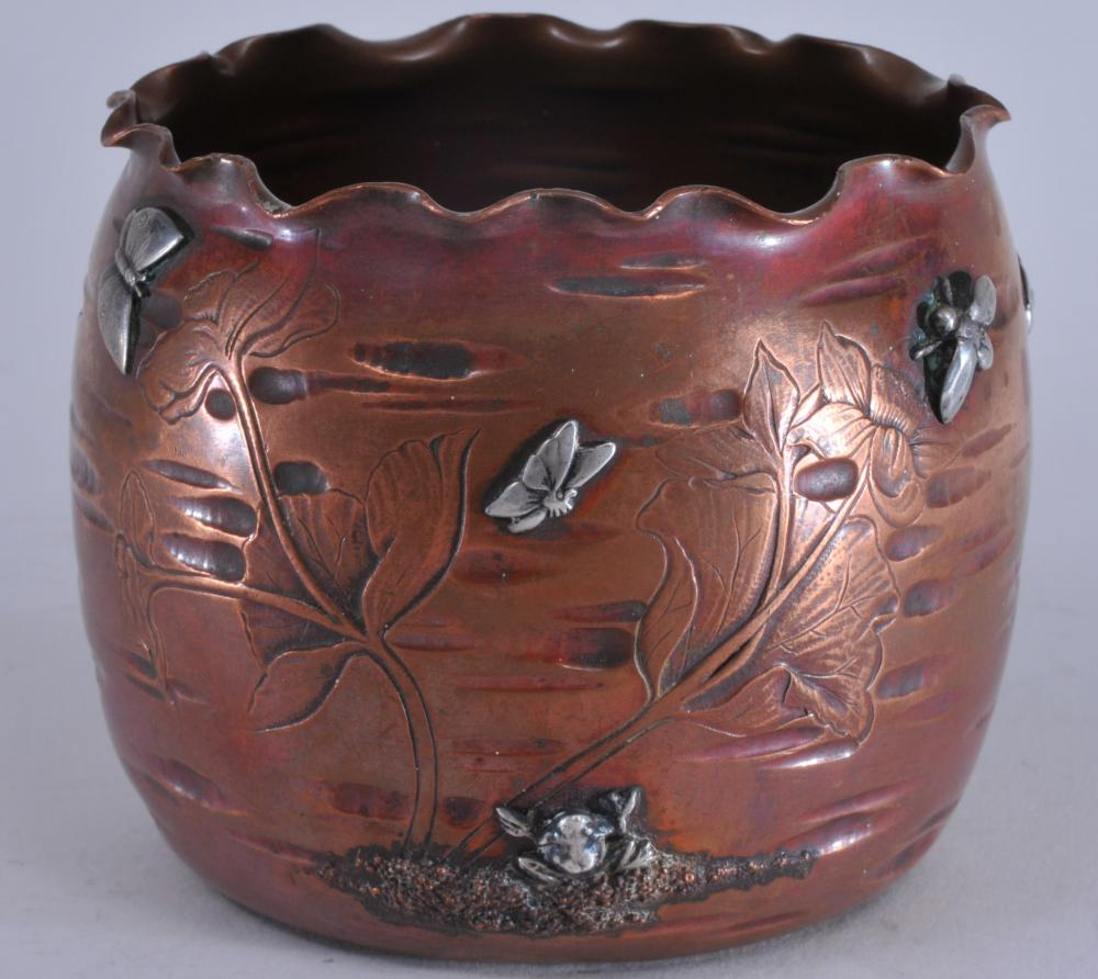 "Lot 48: Gorham mixed metals Aesthetic Movement copper body scalloped edge vase with applied silver bugs, birds, frog and butterfly. Engraved lily pad decoration. Marked on base. Wear to patina. Slight scratches on base. 4"" diameter. 3-1/2"" high."