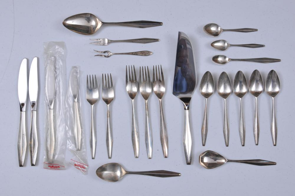 "Lot 54: Reed and Barton sterling silver 23 piece partial flatware set. Mid Century Modern design. Includes (3) forks- 7-1/2"". (2) forks- 7"". (5) teaspoons- 6"". (1) large spoon- 8-1/4"". (1) seafood fork. (1) olive fork. (5) miscellaneous spoons. (4) knives- 8"